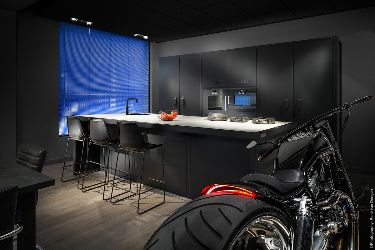 bachelor-kitchen-roaring-motorbike-blue-screen-wndow-black-cabinetry