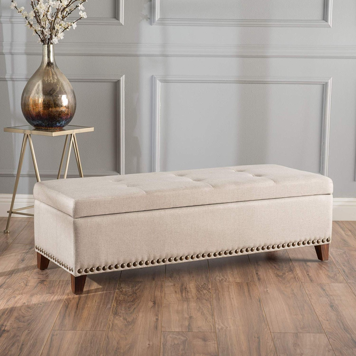 long-storage-bench-with-light-beige-upholstery-and-decorative-nailhead-trim