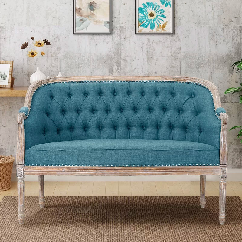 modern-french-provincial-loveseat-with-distressed-wood-frame-and-bright-blue-tufted-upholstery
