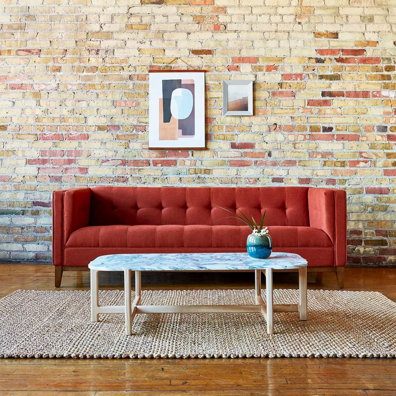 red-orange-designer-sofa-with-track-arms-and-biscuit-tufted-upholstery
