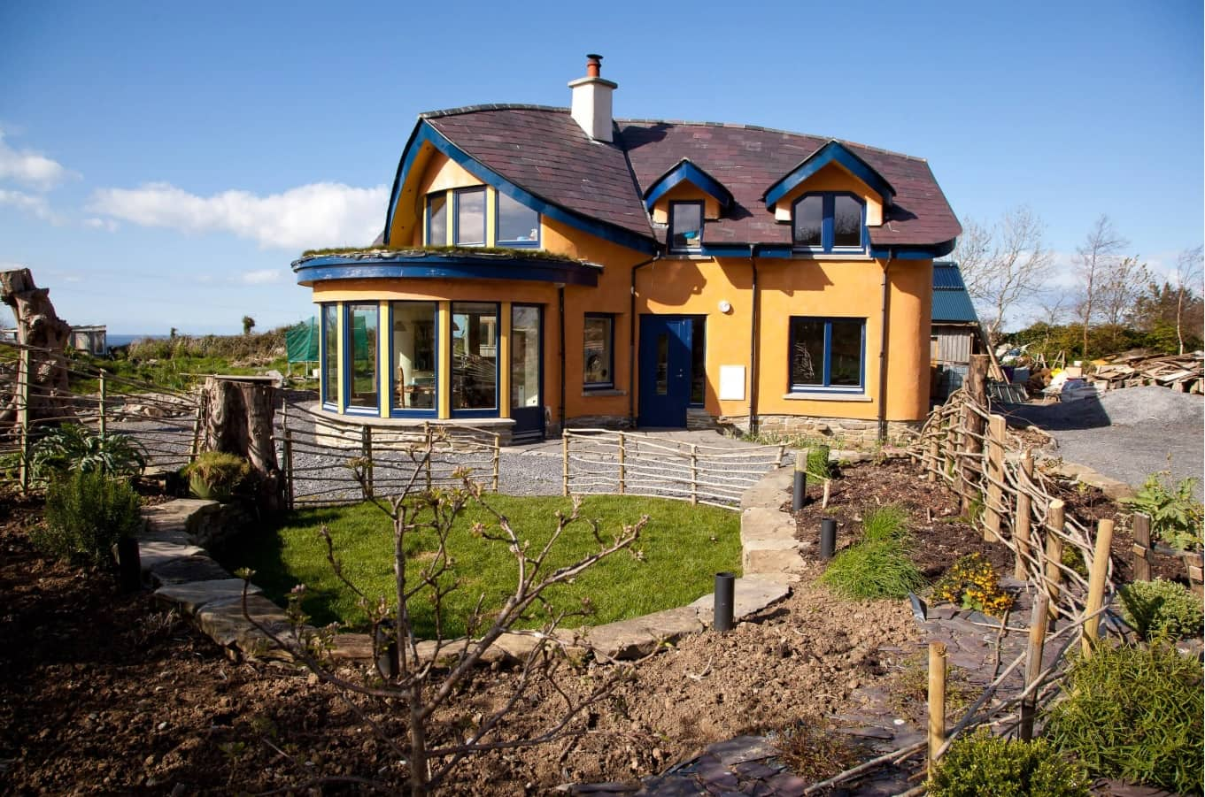 Tiny House on Foundation: Pros and Cons of Living in a Small House. American house with sunroom and cultivated land plot