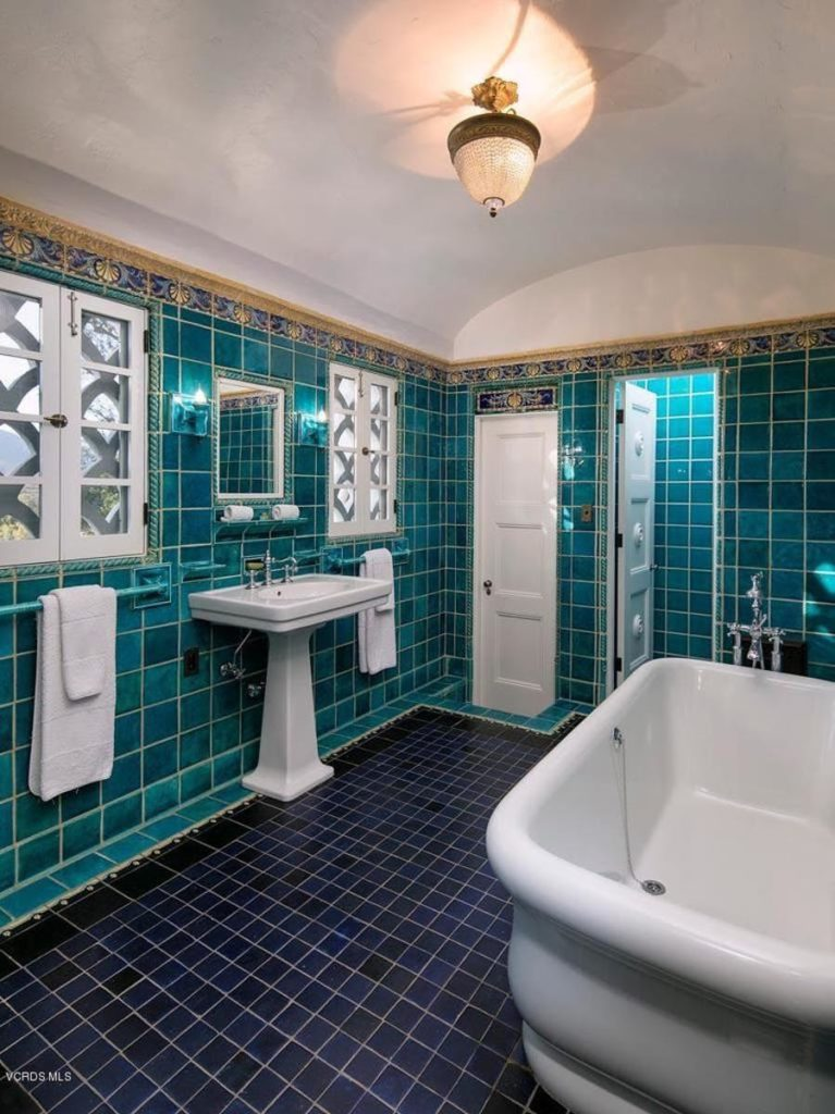 The off-white cove ceiling of this Southwestern-style bathroom is a nice contrast for the dominating green and blue tiles of the walls and flooring. These results in the white porcelain pedestal sink and the white porcelain freestanding bathtub to stand out.
