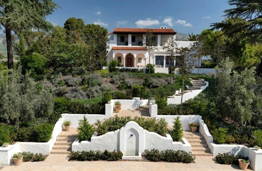 This charming Southwestern-style landscaping has a large white and beige stone structure that has stairs and planters filled with shrubs and pines leading up to the home on top of the hill. The white low walls on the sides are flanked by the thick foliage of the landscape allowing for an awesome walk up the stone steps.
