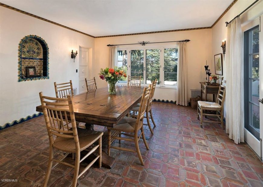 This beautiful dining room has a Southwestern-style flair to its patterned terracotta flooring tiles and the small colorful alcove on the side of the wooden dining set. This alcove has colorful and patterned tiles that make it stand out against the white wall.