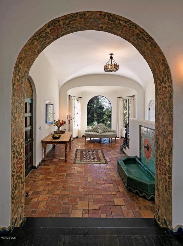 This beautiful Southwestern-style foyer is adorned with a fountain on the side that has eye-catching green tiles with patterns surrounding the water spout. This stands out against the contrasting terracotta flooring and the white walls culminating to a groin arched ceiling.