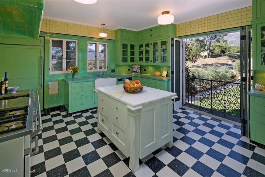 This is a cozy and homey Southwestern-style kitchen with checkered black and white flooring that contrasts the bright green tone of the surrounding cabinets and drawers of the kitchen peninsulas that blend with the walls and the fridge door.