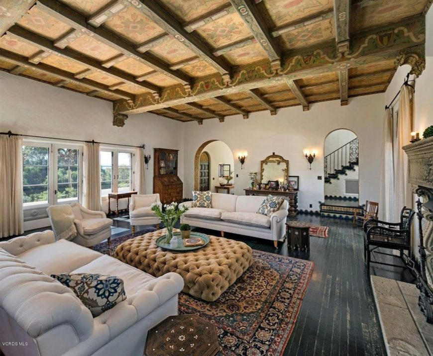 This Southwestern-style living room has distressed black hardwood flooring accented with a colorful patterned area rug topped with a brown tufted coffee table in between the light gray sofa set. These are all under a wooden ceiling that has exposed wooden beams.