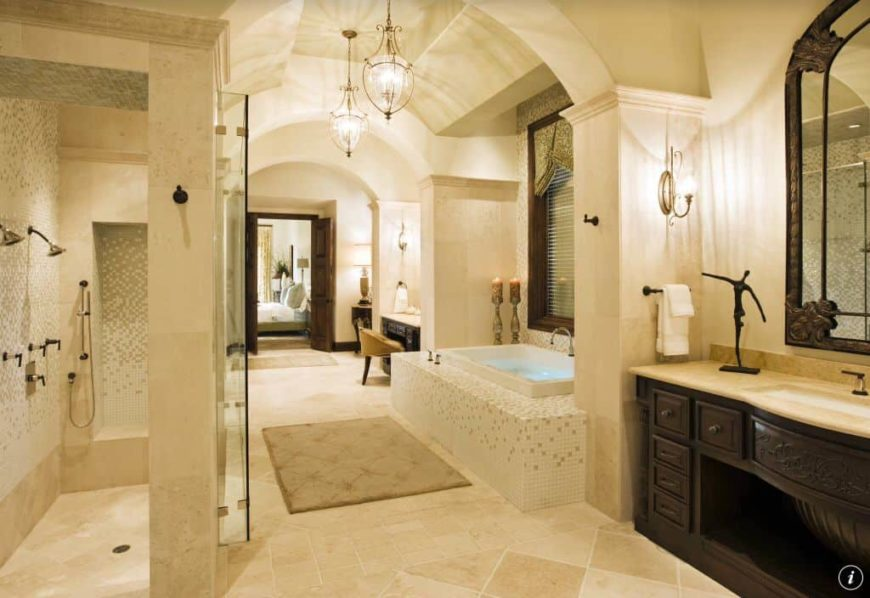 A master suite with a large master bathroom featuring a drop-in tub and a walk-in shower room, together with a powder area. The room is lighted by classy ceiling and wall lights.