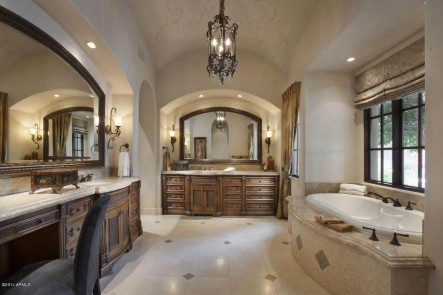 A spacious master bathroom with a tall and elegantly decorated ceiling and tiles flooring. The room offers a drop-in tub and a powder area, along with a large mirror.