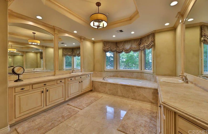 This master bathroom boasts a beautiful tray ceiling and beige tiles flooring. It also has two sink counters and a drop-in tub by the window.