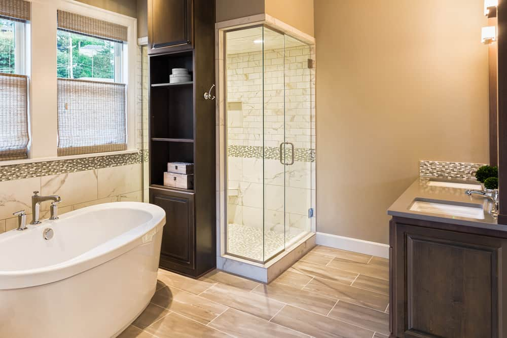 Master bathroom featuring a tall ceiling and hardwood flooring. It offers a deep freestanding tub and a walk-in corner shower, along with a double sink.