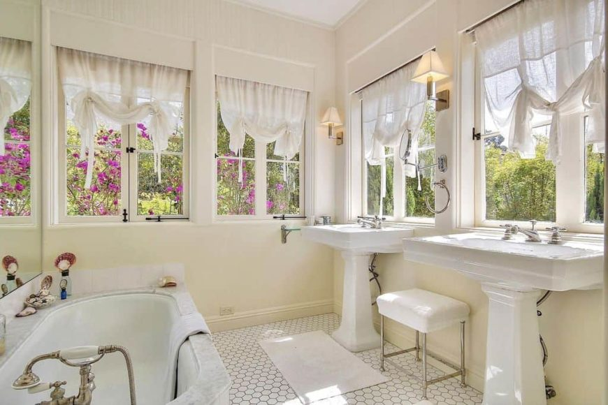 A master bathroom with lovely window curtains and has two pedestal sinks, along with a deep soaking tub on the side.