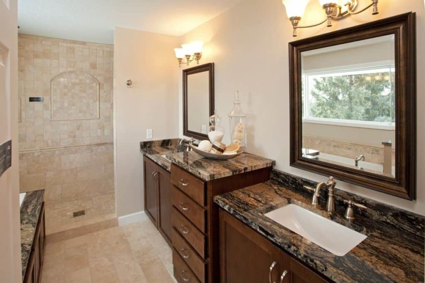 A close up look at this master bathroom's gorgeous sink counters lighted by classy wall lights. The room offers a walk-in shower area.