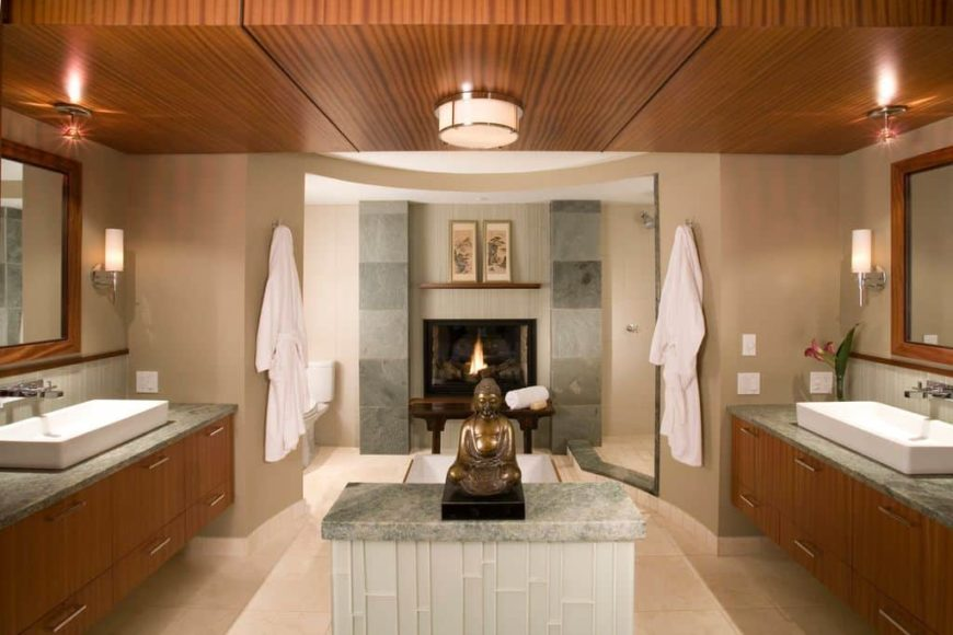 Master bathroom boasting a stunning ceiling and tiles flooring. It offers a walk-in corner shower, a toilet room, a drop-in tub with a fireplace and two floating vanities with vessel sinks.