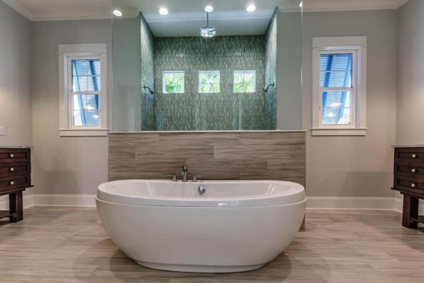 A focused shot at this master bathroom's large freestanding tub set on the hardwood flooring. The room also offers a walk-in shower with stylish walls.