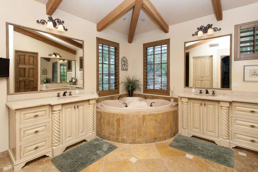 A spacious master bathroom featuring a stunning corner tub along with two sinks lighted by classy wall lights. The room has tiles flooring and a ceiling with exposed beams.