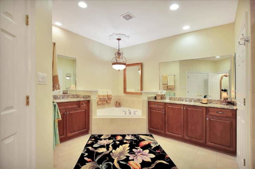 Master bathroom with a drop-in corner tub and two sink counters with granite countertops. The tiles flooring is topped by a stylish area rug.