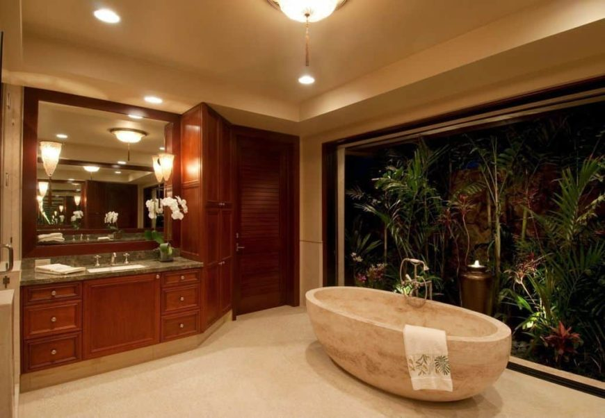 Master bathroom featuring a stylish freestanding tub by the large glass window overlooking the peaceful outdoor view.