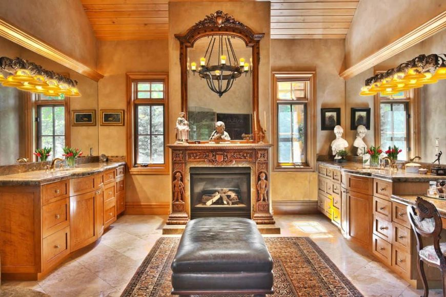 Master bathroom featuring a tall wooden ceiling and tiles flooring. It features two sink counters, a powder area and a fireplace in the middle.