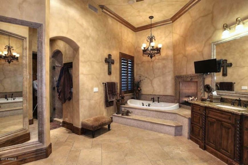 Master bathroom with stylish beige walls and ceiling, along with tiles flooring. The room offers a drop-in tub with a fireplace, a walk-in shower room and a sink counter lighted by wall lights.