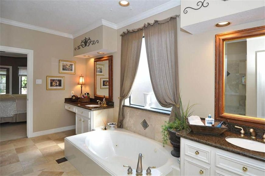 Master bathroom featuring two sink counters with granite countertops and a drop-n tub.