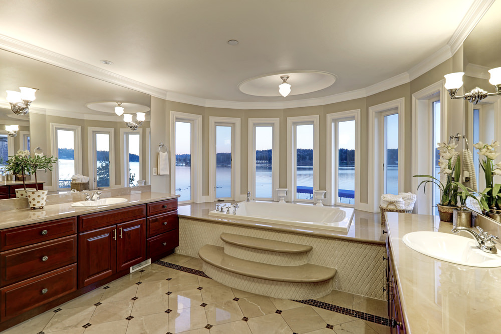 This master bathroom offers a freestanding soaking tub and a walk-in shower room. There are two sink counters, and the room is lighted by a fancy ceiling light.