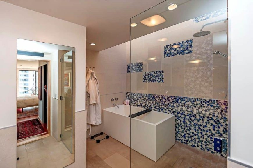This master bathroom offers a beautiful white freestanding deep soaking tub and a walk-in shower area. The blue tiles on the wall look absolutely stylish.