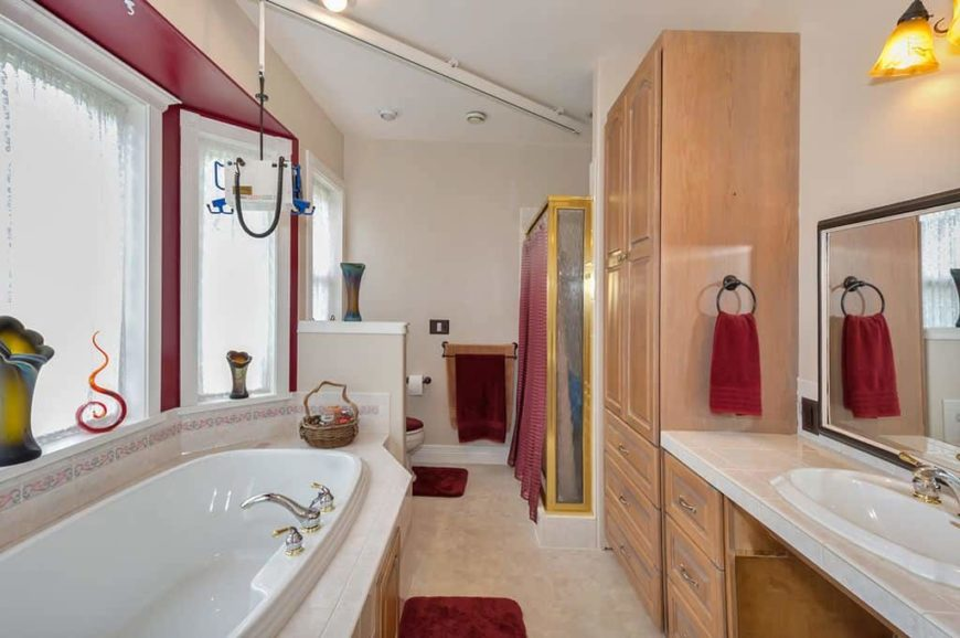 A narrow master bathroom featuring a rustic reach-in closet, along with a walk-in shower, a deep soaking tub and a sink counter lighted by a classy wall light.
