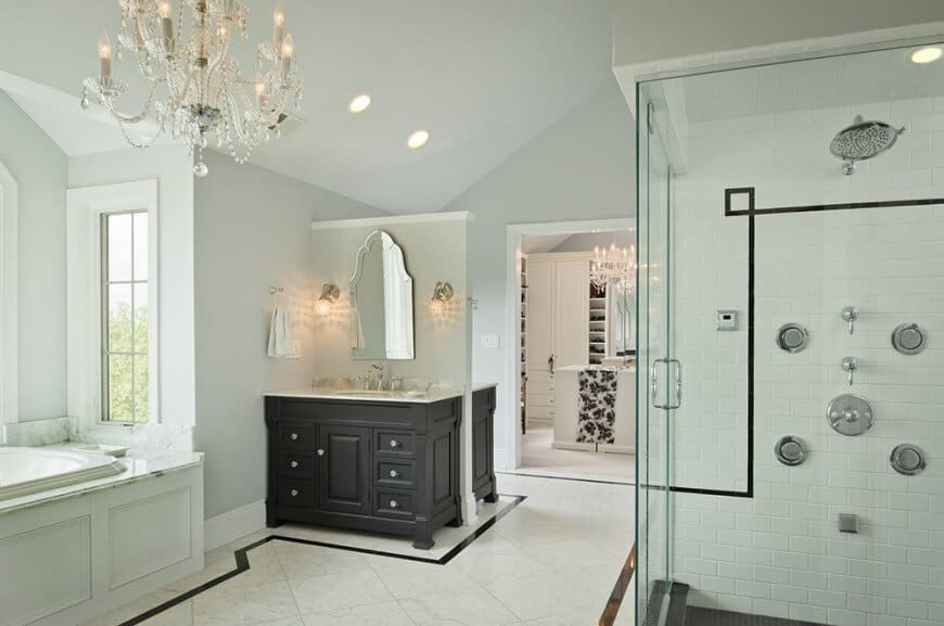 Master bathroom featuring decorated tiles floors and a shed ceiling lighted by a glamorous chandelier. The room offers a walk-in shower and a walk-in closet.