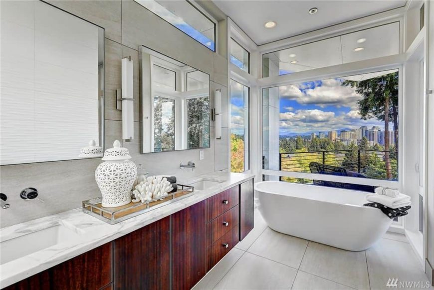 Master bathroom with tiles flooring and glass windows overlooking the stunning outdoor views. The room also has a freestanding deep soaking tub by the windows.