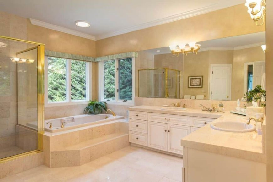 Master bathroom with beige walls and tiles flooring. It offers a walk-in shower, a drop-in tub and two sinks lighted by classy wall lights.