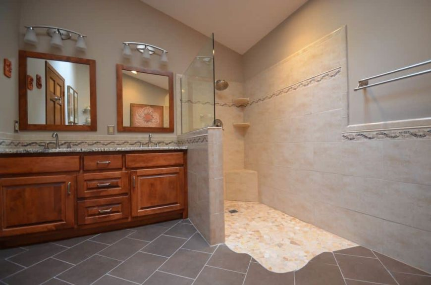 Master bathroom featuring gray tiles flooring. It offers a sink counter with a double sink, along with a walk-in shower.
