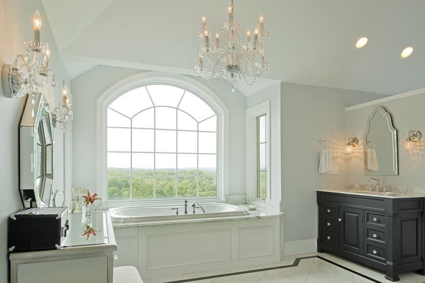 Master bathroom featuring a drop-in tub by the windows and has a sink counter and a powder desk, lighted by a charming chandelier.