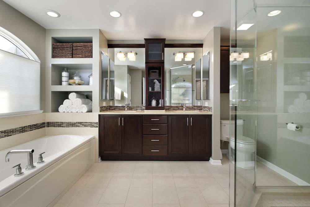 A spacious master bathroom featuring a drop-in deep soaking tub and a walk-in shower room. This bathroom also has a sink counter with two sinks lighted by wall lights.