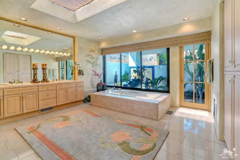 A spacious master bathroom featuring decorated walls and tiles floors topped by an area rug. The room offers a drop-in tub and a sink counter with two sinks.