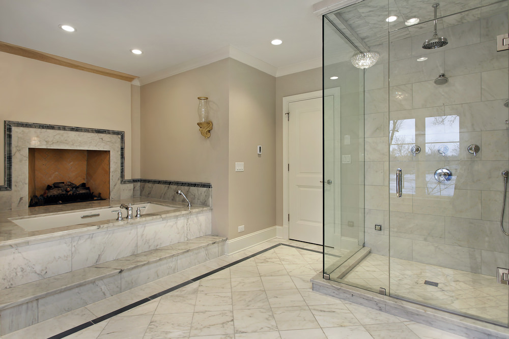 Master bathroom with marble tiles flooring. It also has a drop-in tub with a fireplace along with a walk-in shower room.