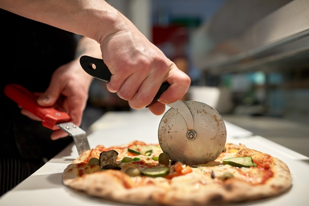 Slicing pizza using a pizza cutter wheels and spatula.