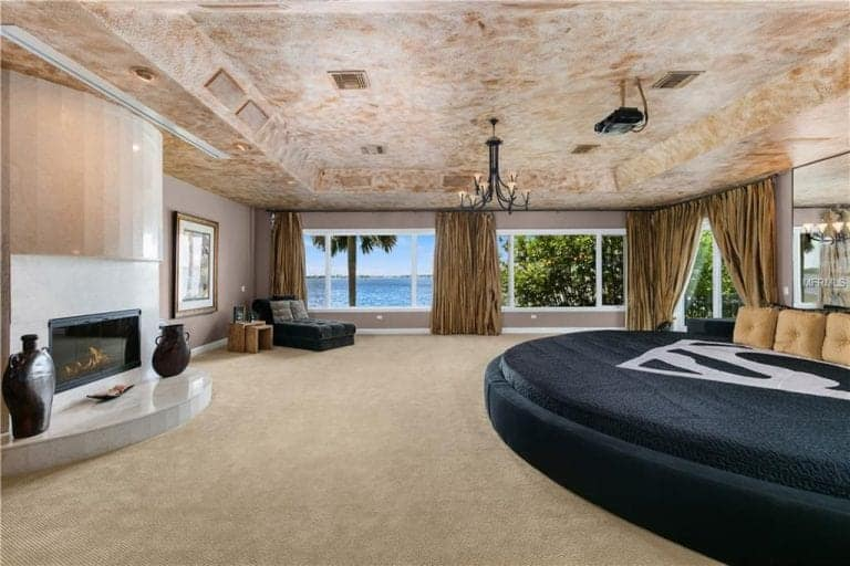 Spacious master bedroom boasts a large round bed facing the fireplace with antique vases along with a tufted chaise lounge by the glass paneled windows overlooking the outdoor scenery. It has carpet flooring and a distressed tray ceiling mounted with a wrought iron chandelier.