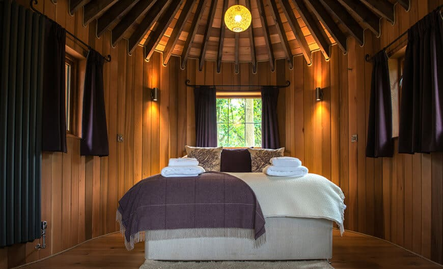 An all wood bedroom showcases a cozy bed and glazed windows dressed in purple curtains. It is illuminated by black sconces and a spherical pendant light that hung from the wood beam ceiling.