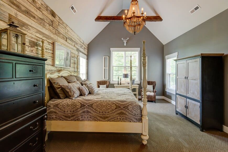 This master bedroom is furnished with wooden cabinets and wingback chairs along with a four-poster bed against the distressed wood plank wall. It includes white wall arts and a warm chandelier that hung from the cathedral ceiling lined with a rustic beam.