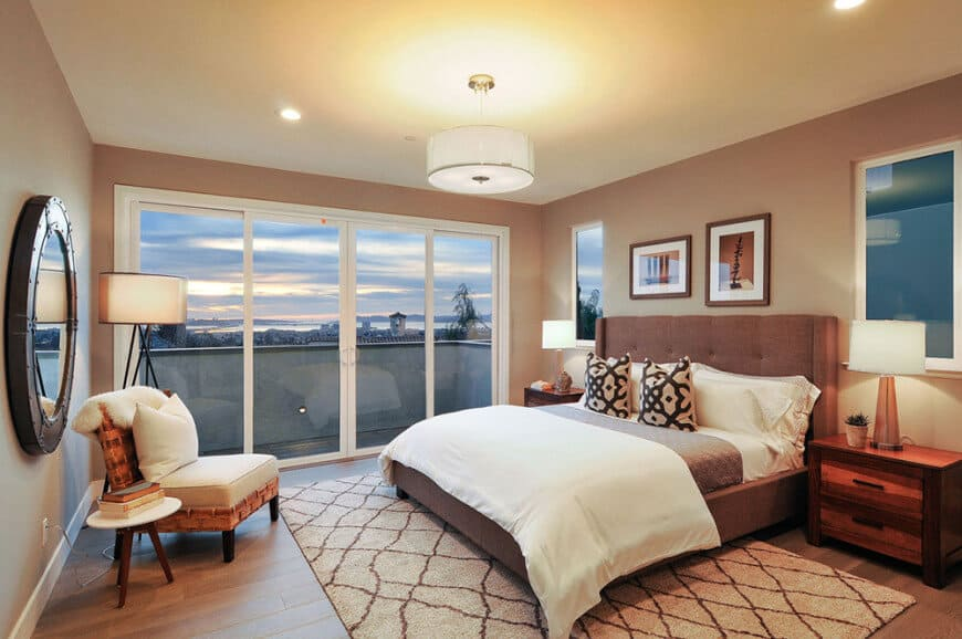 A brown tufted bed flanked by wooden nightstands and sleek table lamps faces the cushioned chair and round mirror mounted on the taupe wall. It is lighted by white drum pendant and recessed ceiling lights.
