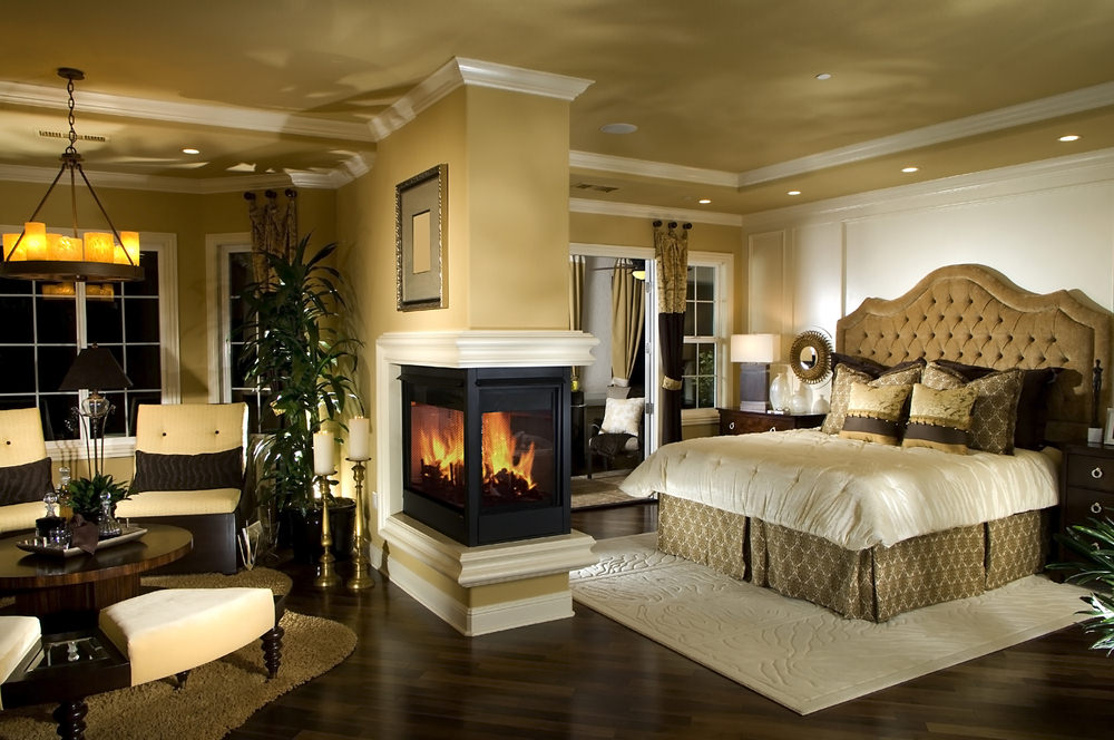 A triple sided fireplace fixed on the beige pillar serves as a divider from the seating area and tufted bed over a cream textured rug. This room is illuminated by a round chandelier and recessed ceiling lights.