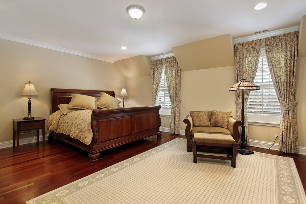 Classic master bedroom boasts a cozy lounge chair and a wooden bed that blends in with the rich hardwood flooring topped by a bordered area rug. It includes flush and recessed ceiling lights along with louvered windows dressed in patterned drapes.