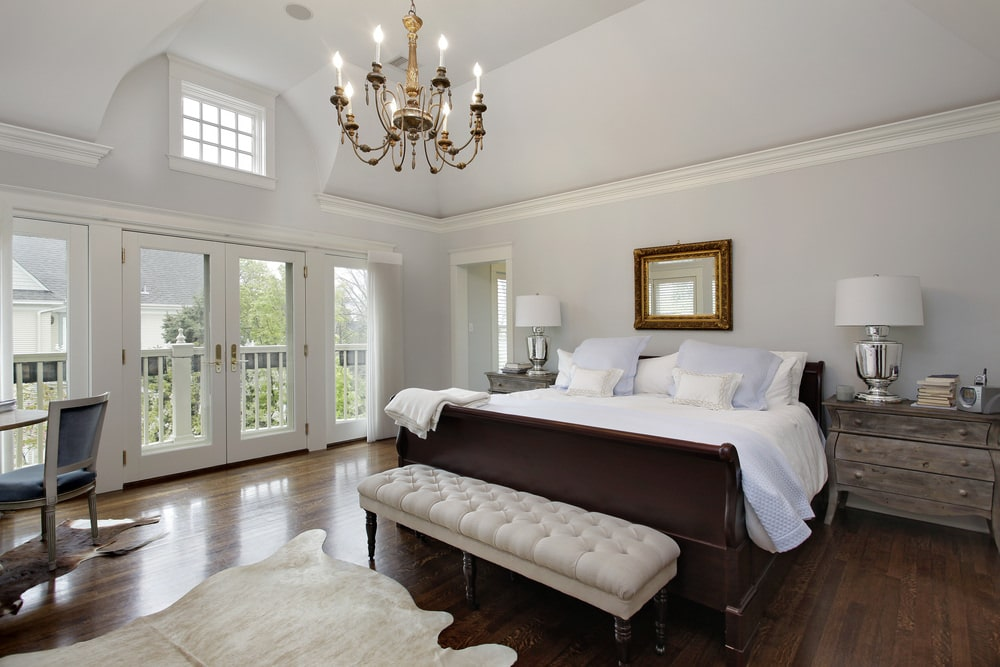 White master bedroom with a candle chandelier and cowhide rugs that lay on the hardwood flooring. It includes rustic nightstands and a dark wood bed with a beige tufted bench on its end.