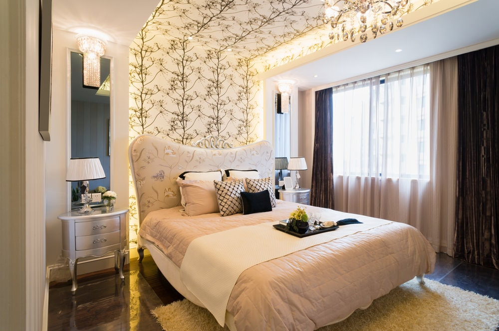 Beige patterned wallpaper extends to the ceiling that's mounted with recessed lights and fancy chandeliers. This room features chrome nightstands and a charming floral bed that sits on a shaggy area rug and dark hardwood flooring.