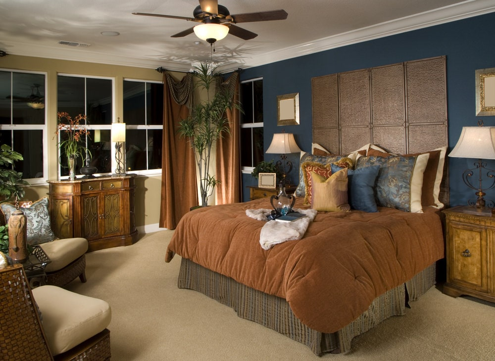 Tropical master bedroom with carpet flooring and multi-colored walls fitted with white framed windows. It includes a skirted bed and wicker chairs topped with beige cushions.
