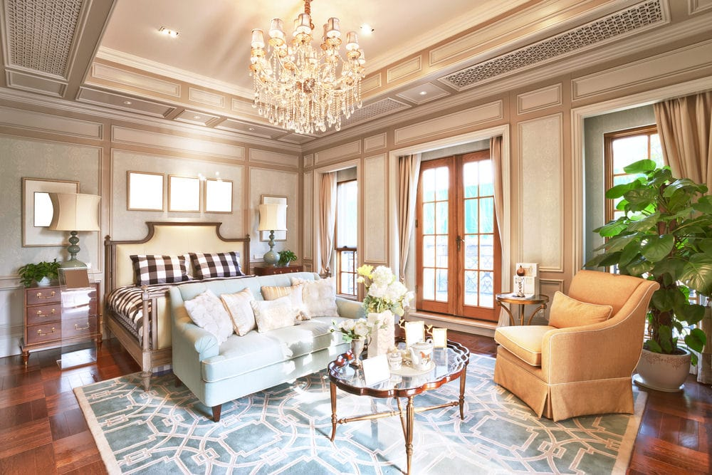 Elegant master bedroom illuminated by recessed lights and a fabulous crystal chandelier that hung from the tray ceiling. It showcases an upholstered bed dressed in checkered bedding along with a seating area over a blue patterned rug.