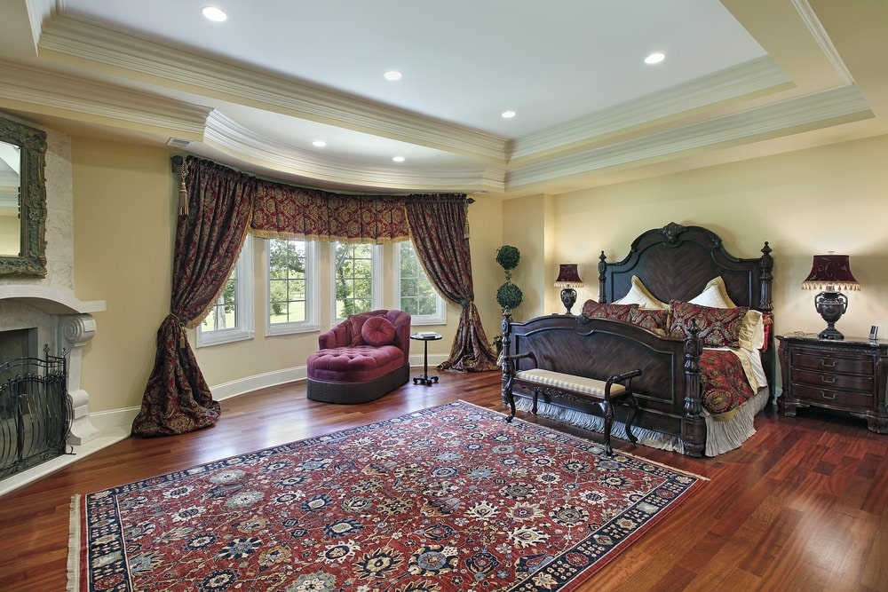 The sophisticated master bedroom showcases a dark wood bed and a red tufted chaise lounge by the bay window dressed in classic drapes and valance. It includes a printed rug and a fireplace with an ornate mirror on top.