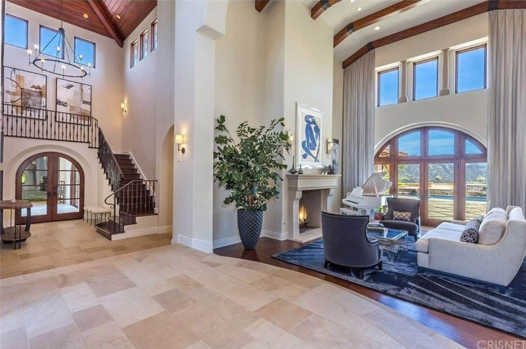 This foyer features an arched double door and a stylish console table over beige limestone flooring. It includes white cushioned seats and a round chandelier that hung from the high cathedral ceiling.