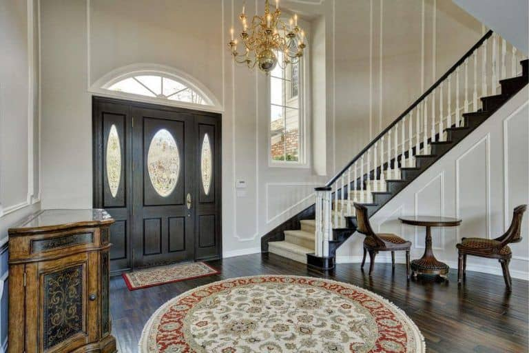 A fancy gilded chandelier illuminates this foyer showcasing an antique console table and classic patterned rugs over the dark hardwood flooring. It is completed with a seating area and a large entry door matching with the stairs' stringers.